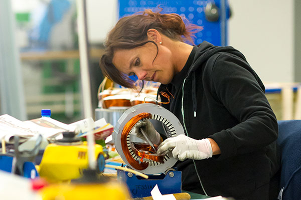 Woman winding an electric motor by hand in a workshop.